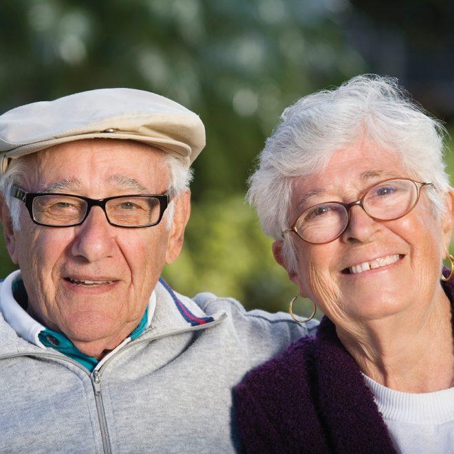 Senior couple smiling outside