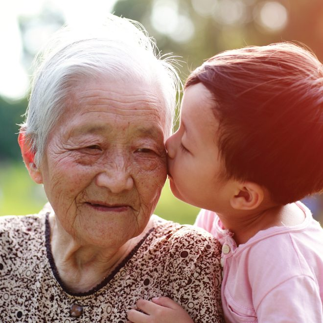 senior woman getting a kiss from a little boy on the cheek