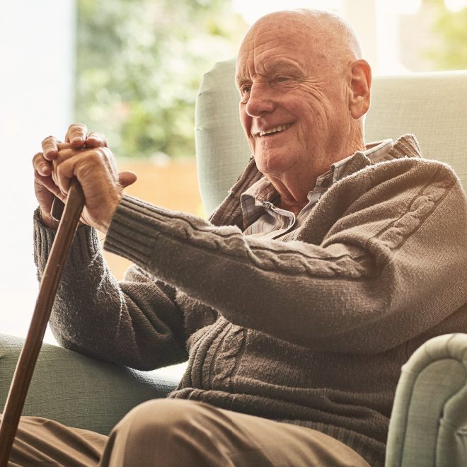 senior man holding a cane and sitting in a comfortable chair