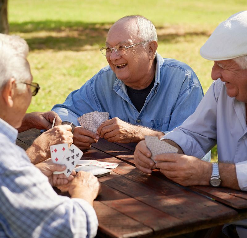 group of senior men playing cards