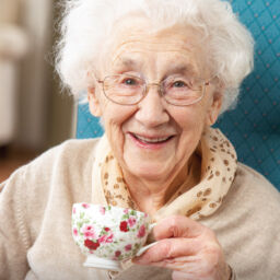 Happy senior woman drinking a warm cup of tea