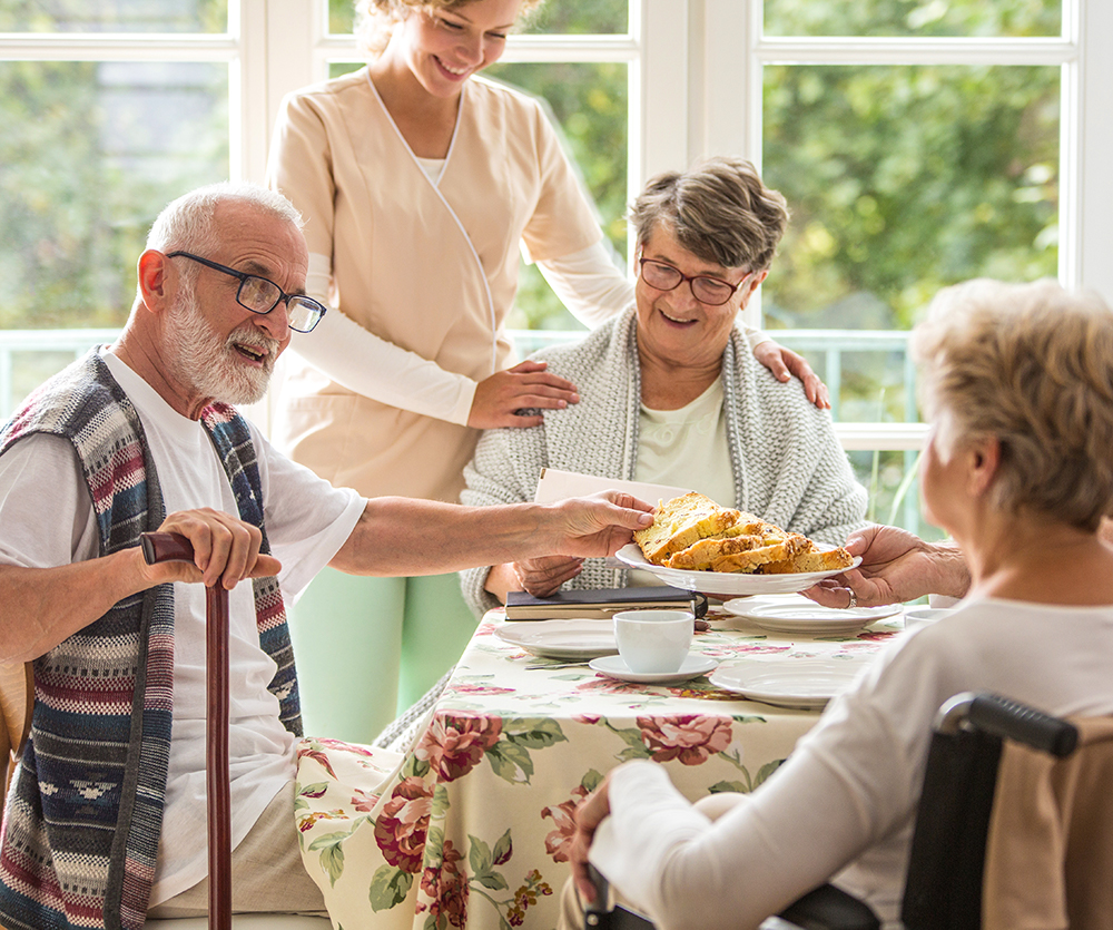 Female Staff member enjoying time with residents while they have breakfast