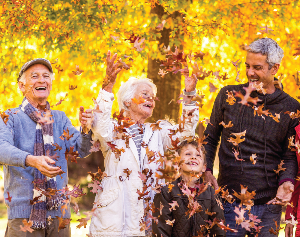 Senior couple throwing leaves with adult son and grandson