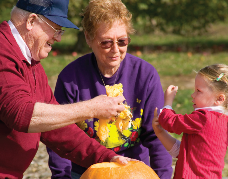 Grandparents carving a pumpkin with their granddaughter