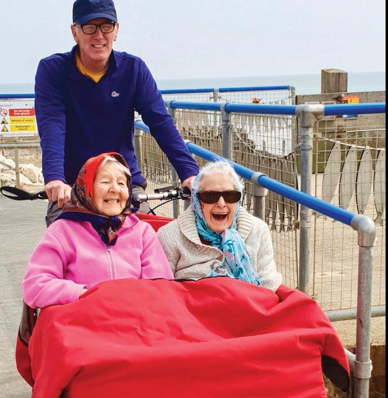 Two senior women being pushed on a trishaw piloted bike ride