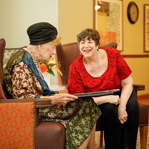 Senior resident looking at a photo album with a friend.