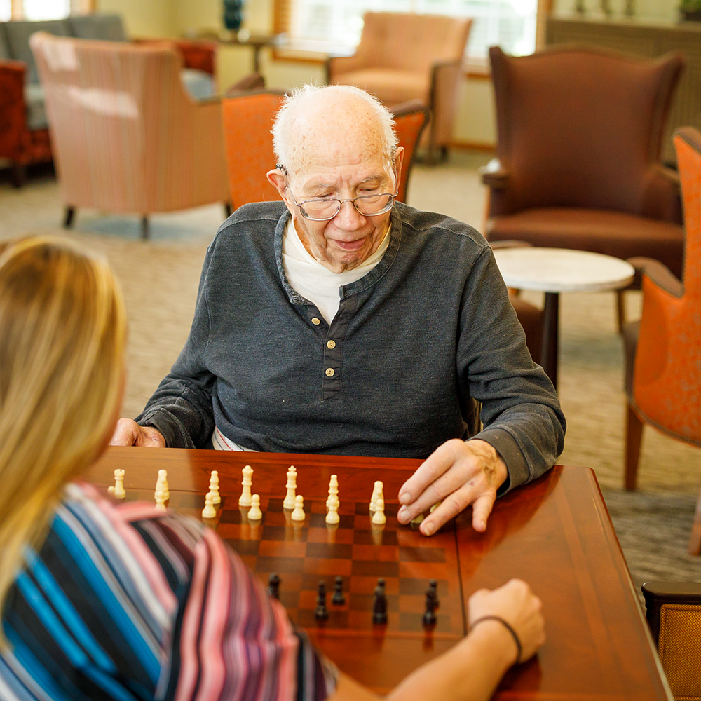 senior man playing chess with a team member
