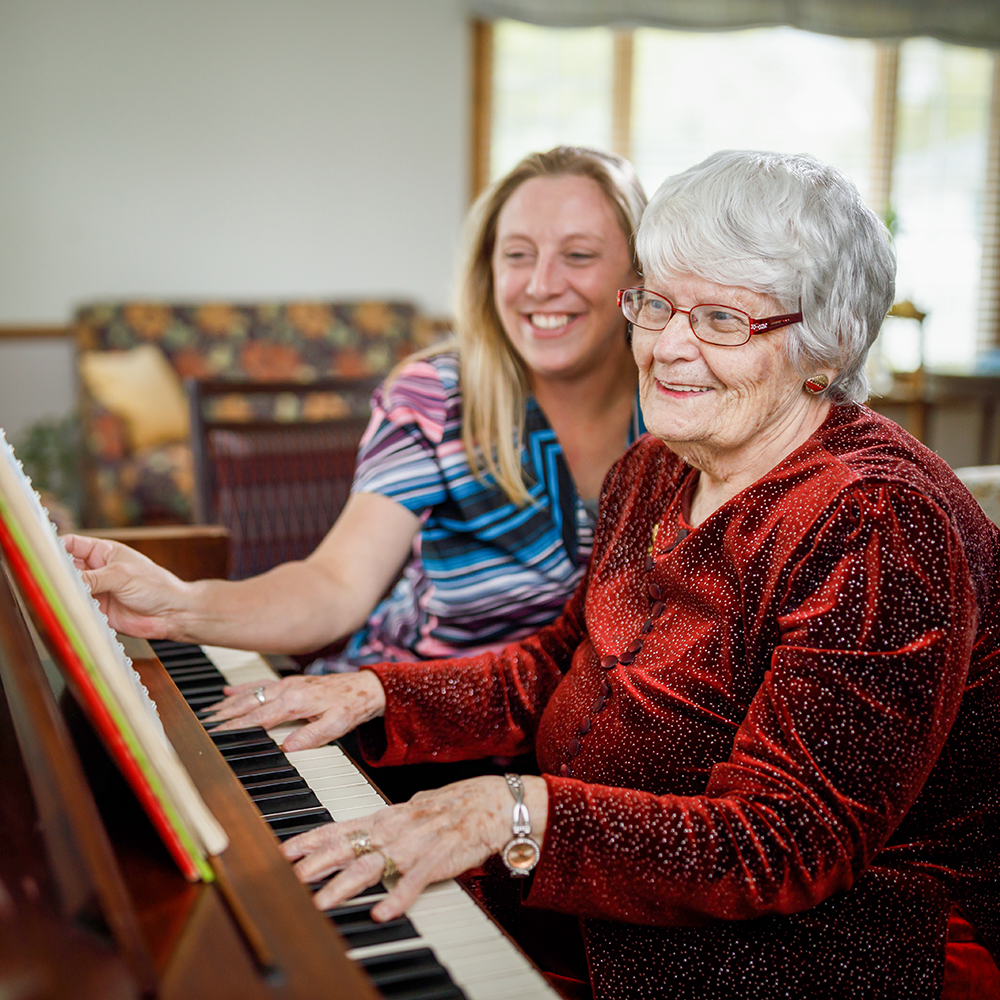 Staff member playing the piano with a resident